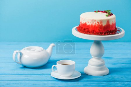 Photo for Cake decorated with red currants near white cup and tea pot isolated on blue - Royalty Free Image