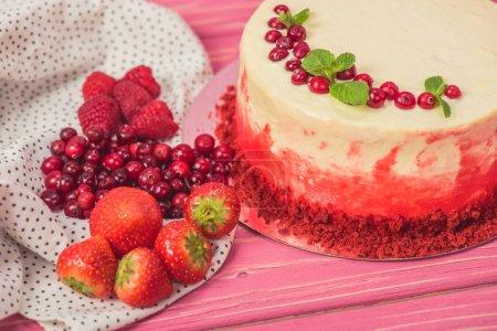 Photo pour Gros plan de gâteau blanc décoré de groseilles rouges et de feuilles de menthe près d'autres fruits - image libre de droit