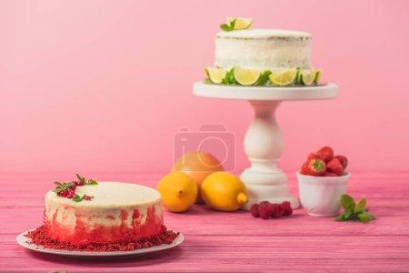 Photo pour Gâteau décoré de groseilles et feuilles de menthe près de fruits et gâteau blanc sur une surface en bois rose isolé sur rose - image libre de droit