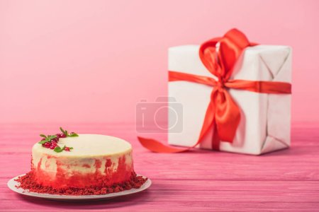 Photo for Cake decorated with currants and mint leaves near gift box isolated on pink - Royalty Free Image