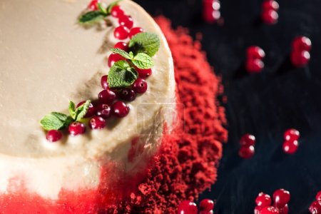 Photo for Close up of white cake decorated with mint leaves near red currants isolated on black - Royalty Free Image