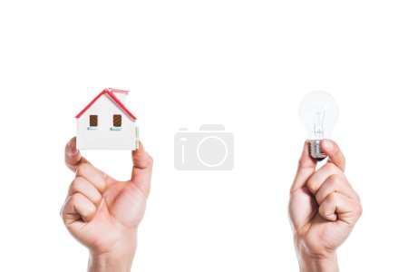 Photo for Cropped view of male hands holding house model and led lamp in hands isolated on white, energy efficiency at home concept - Royalty Free Image