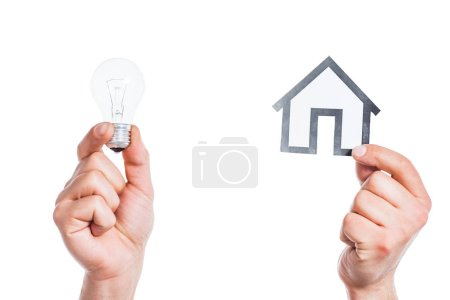 Photo for Cropped view of male hands holding paper house and led lamp in hands isolated on white, energy efficiency at home concept - Royalty Free Image