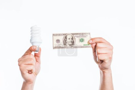 cropped view of male hands holding fluorescent lamp and hundred dollar banknote in hands isolated on white, energy efficiency concept