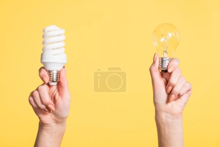 cropped view of woman holding fluorescent and led lamps in hands isolated on yellow, energy efficiency concept