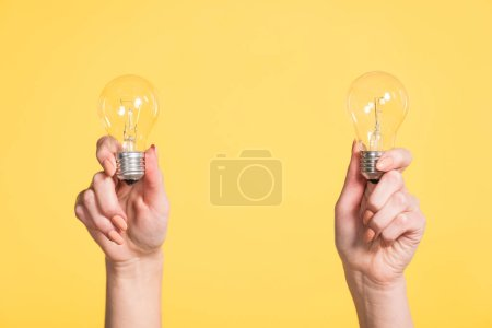 Photo for Cropped view of woman holding led lamps in hands isolated on yellow, energy efficiency concept - Royalty Free Image