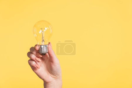 Photo for Cropped view of woman holding led lamp in hands isolated on yellow, energy efficiency concept - Royalty Free Image