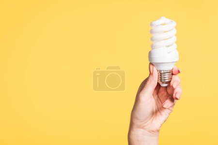 Photo for Cropped view of female hand holding fluorescent lamp isolated on yellow, energy efficiency concept - Royalty Free Image