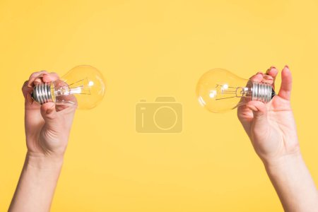 cropped view of female hands holding led lamps isolated on yellow, energy efficiency concept