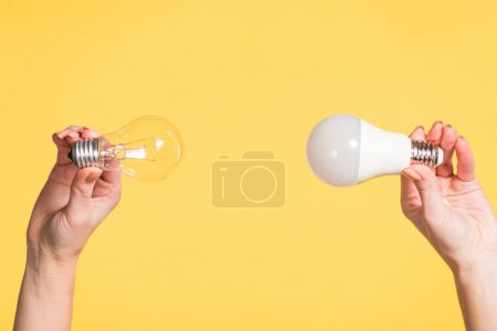 Photo for Cropped view of female hands holding led and fluorescent lamp isolated on yellow, energy efficiency concept - Royalty Free Image