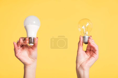 cropped view of female hands choosing between led and fluorescent lamps isolated on yellow, energy efficiency concept
