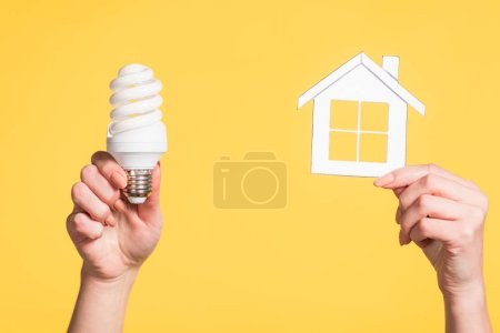 Photo for Cropped view of female hands holding paper house and fluorescent lamp in hands isolated on yellow, energy efficiency at home concept - Royalty Free Image