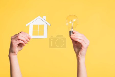 Photo for Cropped view of female hands holding paper house and led lamp in hands isolated on yellow, energy efficiency at home concept - Royalty Free Image