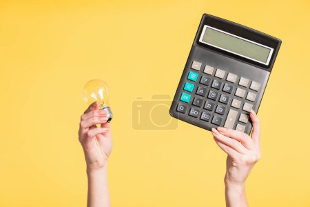 Photo for Cropped view of woman holding led lamp and calculator in hands isolated on yellow, energy efficiency concept - Royalty Free Image