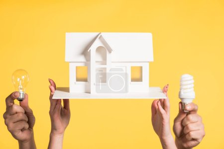 cropped view of woman holding carton house model near man with led and fluorescent lamps isolated on yellow, energy efficiency at home concept