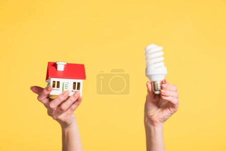 cropped view of woman holding fluorescent lamp and house model in hands isolated on yellow, energy efficiency at home concept
