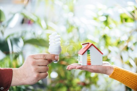 Photo for Cropped view of man holding fluorescent lamp near woman with carton house in hand, energy efficiency at home concept - Royalty Free Image