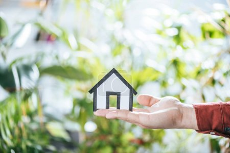 cropped view of paper house in hand of man, energy efficiency at home concept