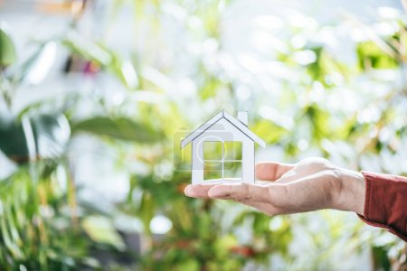 cropped view of man holding paper house in hands, energy efficiency at home concept