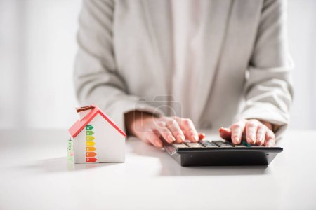 cropped view of woman using calculator near carton house on white background, energy efficiency at home concept