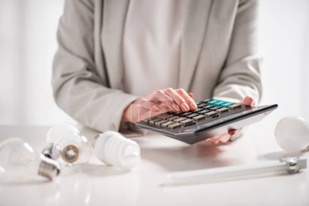 cropped view of woman using calculator near lamps on white background, energy efficiency concept
