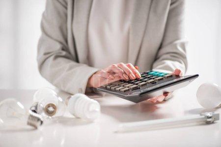 Photo pour Vue recadrée de la femme à l'aide d'une calculatrice près des lampes sur fond blanc, concept d'efficacité énergétique - image libre de droit