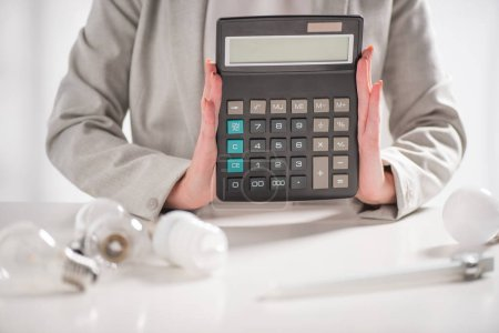 cropped view of woman holding calculator near lamps on white background, energy efficiency concept