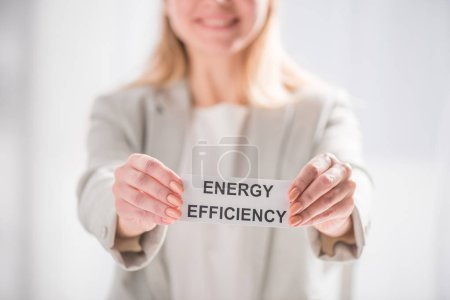 selective focus female hands holding card on white background, energy efficiency concept