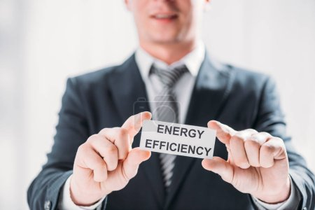 Photo for Selective focus male hands of businessman holding card with lettering on white background, energy efficiency concept - Royalty Free Image