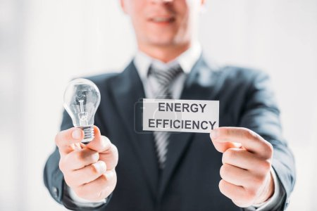 Photo for Selective focus of card and led lamp in male hands of businessman on white background, energy efficiency concept - Royalty Free Image