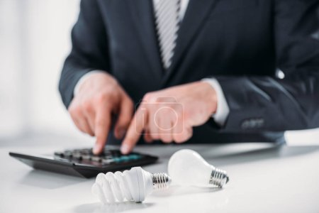 selective focus of fluorescent lamps near businessman in suit using calculator on white background, energy efficiency concept