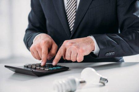 Photo pour Vue recadrée d'homme d'affaires en costume à l'aide de calculatrice près de lampes fluorescentes sur fond blanc, concept d'efficacité énergétique - image libre de droit