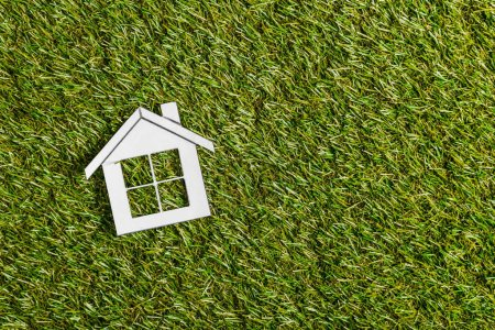top view of white paper house on green grass, energy efficiency at home concept