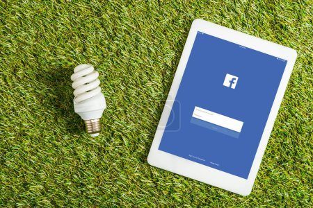 Photo for Top view of fluorescent lamp near digital tablet with facebook app on screen on green grass, energy efficiency concept - Royalty Free Image
