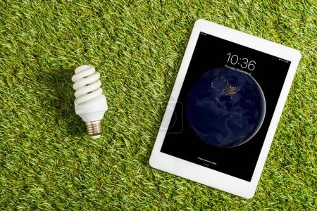 Photo for Top view of fluorescent lamp near digital tablet with lock screen on green grass, energy efficiency concept - Royalty Free Image