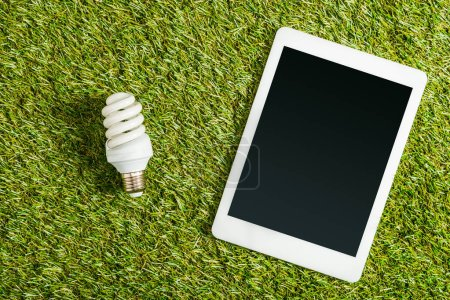 Photo for Top view of fluorescent lamp near digital tablet with blank screen on green grass, energy efficiency concept - Royalty Free Image