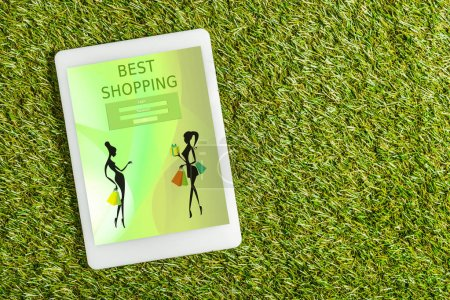 Photo for Top view of digital tablet with shopping app on screen on green grass, energy efficiency concept - Royalty Free Image