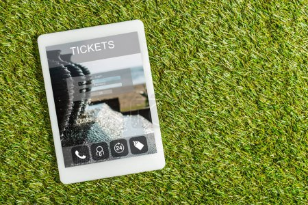 Photo for Top view of digital tablet with tickets app on screen on green grass, energy efficiency concept - Royalty Free Image