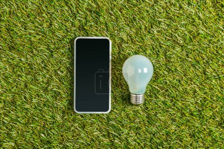 top view of fluorescent lamp near smartphone with blank screen on green grass, energy efficiency concept