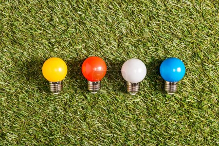 flat lay of colorful fluorescent lamps on green grass, energy efficiency concept