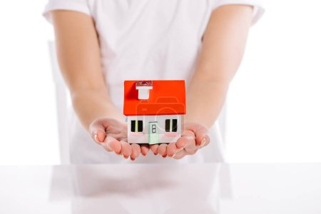 cropped view of woman holding house model isolated on white, mortgage concept