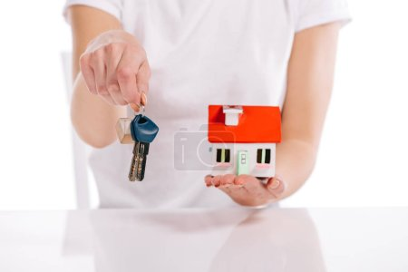 cropped view of woman holding house model and keys isolated on white, mortgage concept