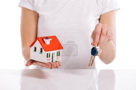 partial view of woman holding house model and keys isolated on white, mortgage concept