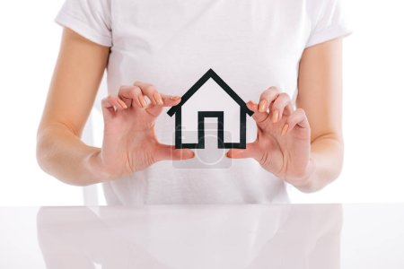 partial view of woman holding house model in hands isolated on white, mortgage concept
