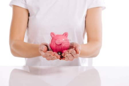 cropped view of woman holding pink piggy bank isolated on white