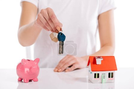 partial view of woman holding keys near house model and piggy bank isolated on white, mortgage concept