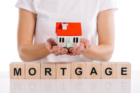 cropped view of woman holding house model near wooden cubes with mortgage lettering isolated on white