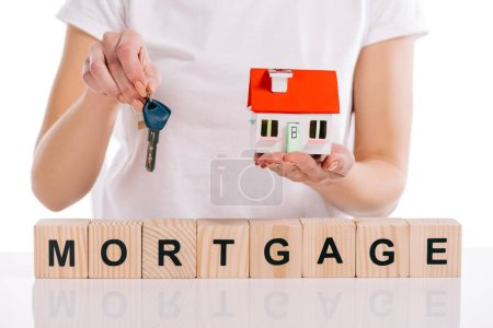 partial view of woman holding house model and keys near wooden cubes with mortgage lettering isolated on white