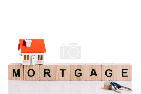 Photo for Wooden blocks with mortgage lettering, house model and keys isolated on white - Royalty Free Image