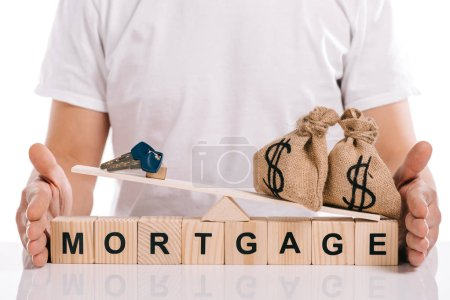 cropped view of man holding scales with moneybags and keys on cubes with mortgage lettering isolated on white
